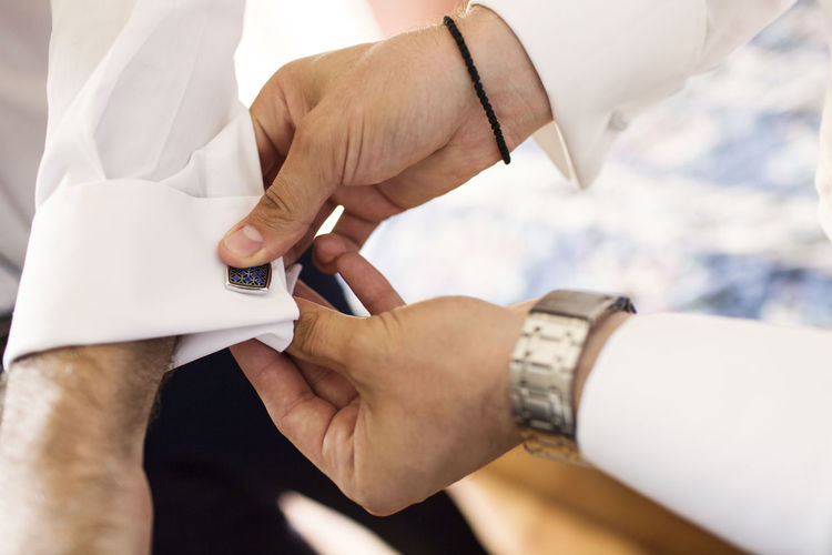 Cropped hands of man buttoning bridegroom cuff link