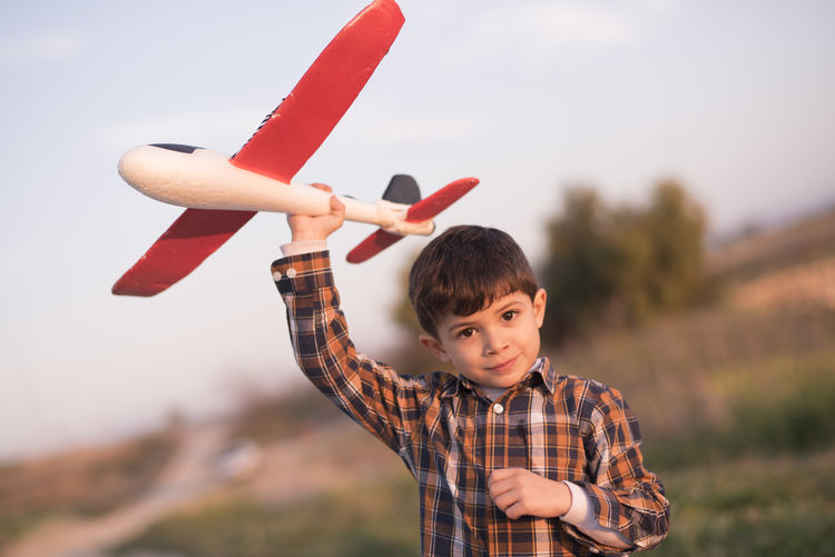 Portrait of boy holding toy airplane standing against sky