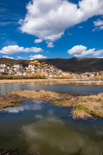 Cloud - Sky Water Sky Building Exterior Architecture Built Structure Reflection Building Nature City Day Waterfront No People Residential District Lake Beauty In Nature Scenics - Nature Outdoors Blue Cityscape TOWNSCAPE Temple Shangrila Shangri-La Yunnan China Tibet Religion Mountain