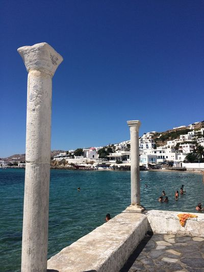 Columns by sea against clear blue sky at mykonos