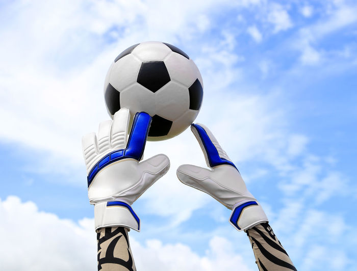 Cropped hand of goalie touching soccer ball against blue sky