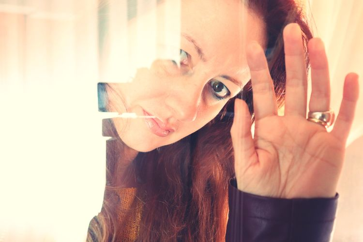 Portrait Of Mature Woman Looking Through Window With Reflection