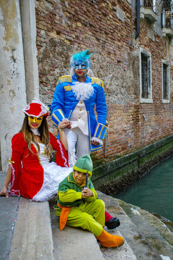 Carnival Carnivale In Venice Architecture Bonding Boys Building Exterior Built Structure Carnival Costumes Child Childhood Day Elementary Age Family Full Length Leisure Activity Lifestyles Men Mother Outdoors Real People Sitting Son Togetherness Women