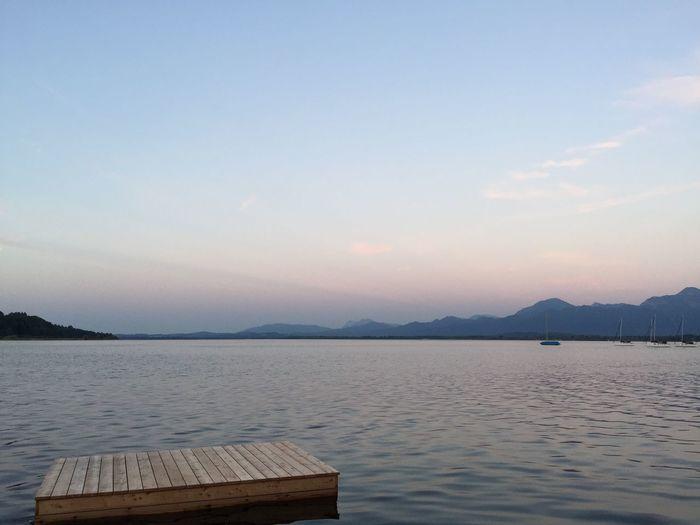 Diving platform in lake against sky at dusk