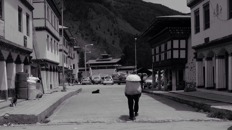 The Following to the market in Paro Bhutan. B&W Bhutan photo essay http://bit.ly/1q7cCqD B&w Street Photography Everybodystreet Blackandwhite Black And White Lifestyles Travel Photography Street Photography Fujifilm_xseries B&w Photography Paro Bhutan On The Road Himalayas Mountain Range Cloudy Sky One Person Leading Lines Solitary Figure Walking Alone Street Dogs Medieval Architecture Mountain Town Looking Away Back Street