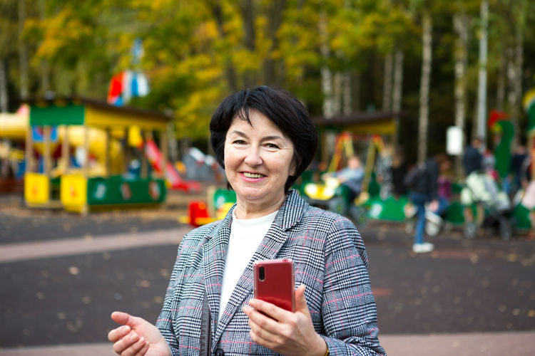 Portrait of smiling woman holding smart phone while standing outdoors