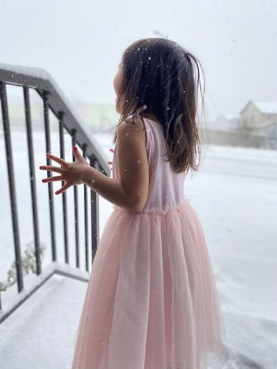 Girl looking away while standing against white snow