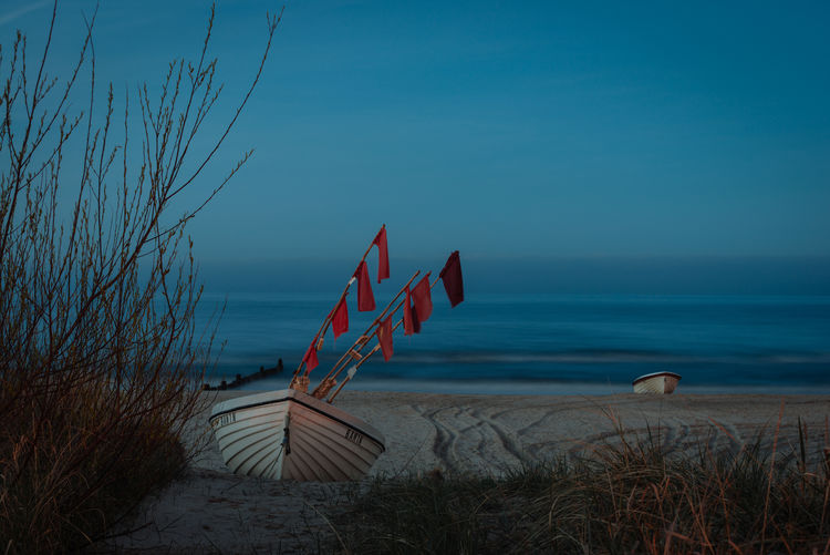 Boat Moored At Beach Against Blue Sky At Dusk