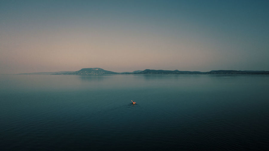 A lone paddler faces the north shore of lake balaton, the largest lake in central europe.