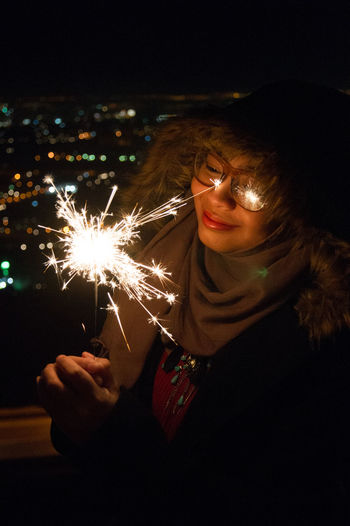 Smiling woman holding illuminated sparkler by window at night
