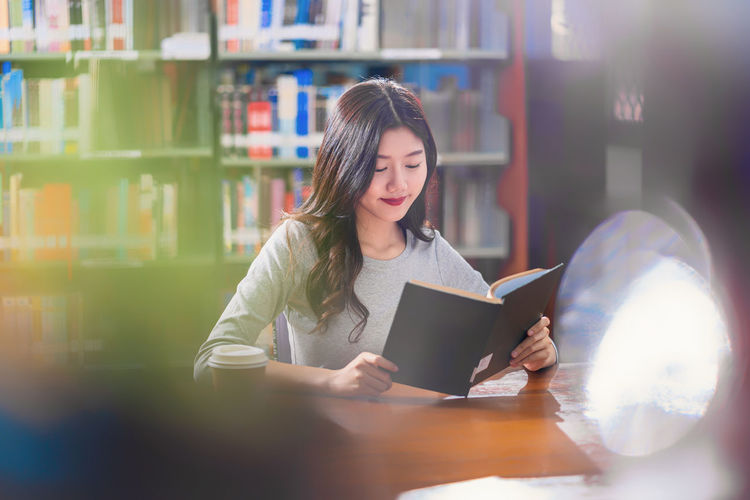 Young woman looking away while sitting on book