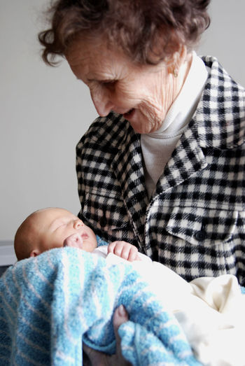 A grandmother holding her newborn grandchild. Baby Bonding Care Child Childhood Family Grandchild Indoors  Innocence Love Positive Emotion Senior Adult Senior Women Togetherness Two People