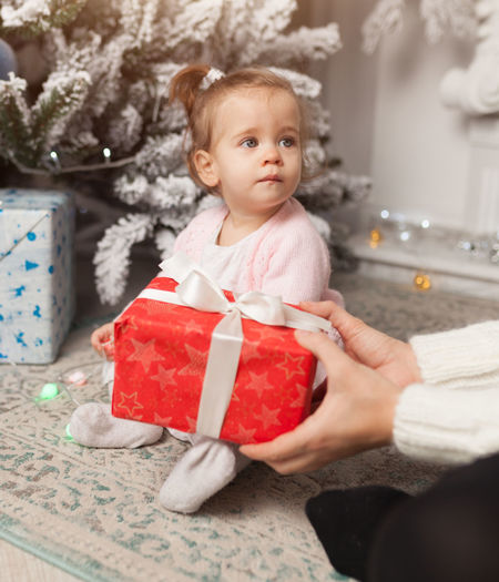 Cropped image of mother giving gift to daughter during christmas