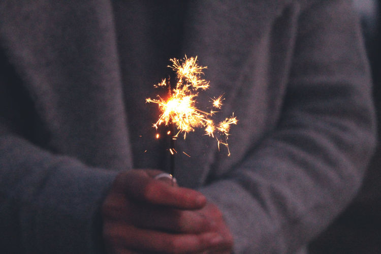 Midsection Of Person Holding Sparkler At Night