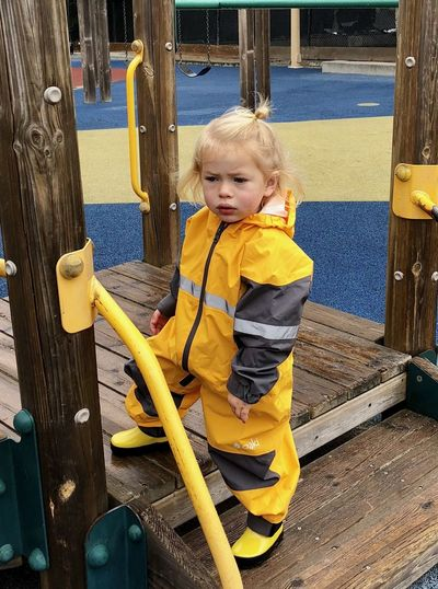 Full length of boy wearing raincoat while standing in playground