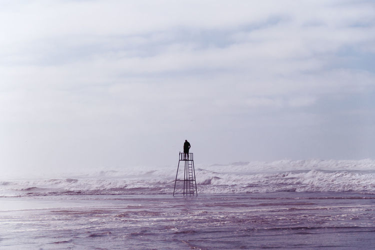 Man Standing On Lifeguard Hut Against Sky At Beach