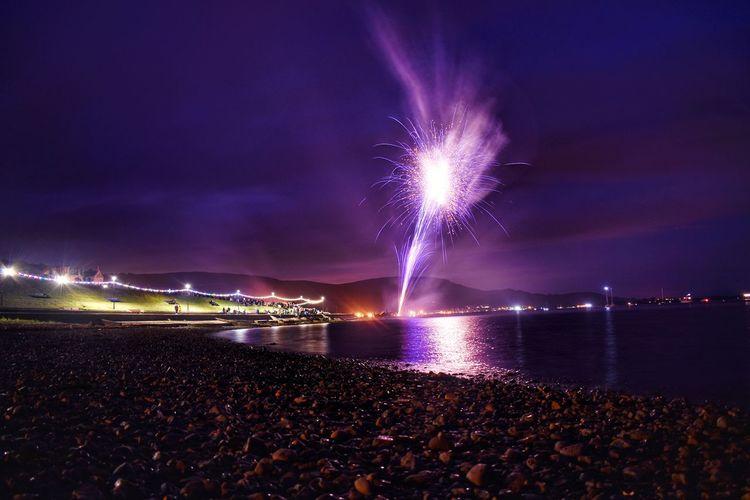 Firework display over sea at night