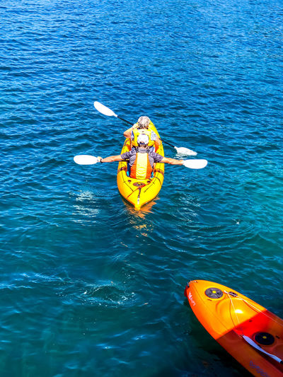 Kayaking Adventure Day Floating On Water High Angle View Kayak Life Jacket Lifestyles Mode Of Transportation Nature Nautical Vessel Outdoors Real People Safety Sea Transportation Water Yellow