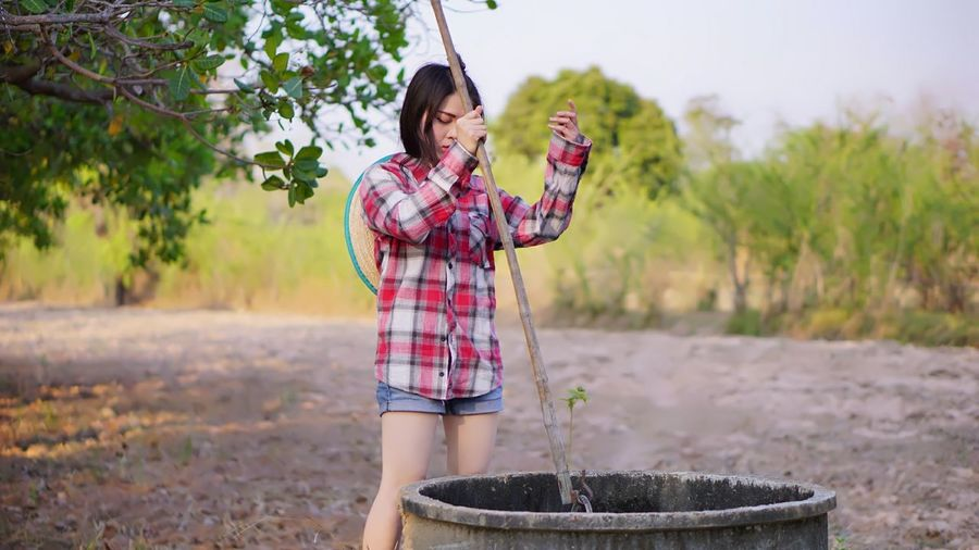Young woman using mobile phone while standing on land