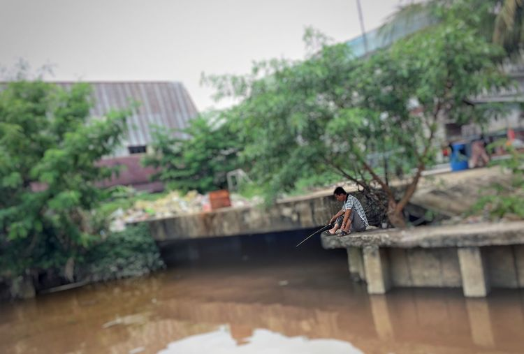 Fishing. One Person Only Architecture Day Building Exterior Built Structure Outdoors Focus On Foreground Fishing One Person Real People Nature Men Squat IPhoneography Blurred Motion Water People