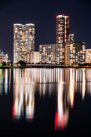 Reflection of illuminated buildings in sea at night