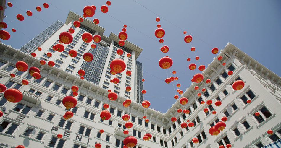Low angle view of lanterns hanging by building against sky