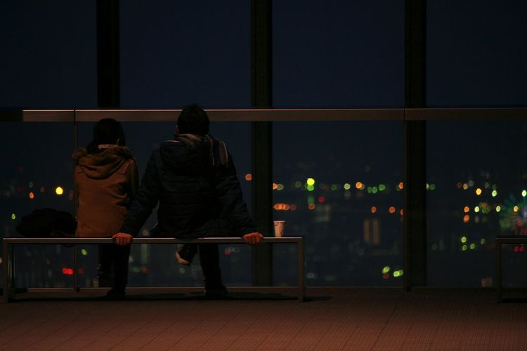 Rear view of couple sitting on bench at promenade during night
