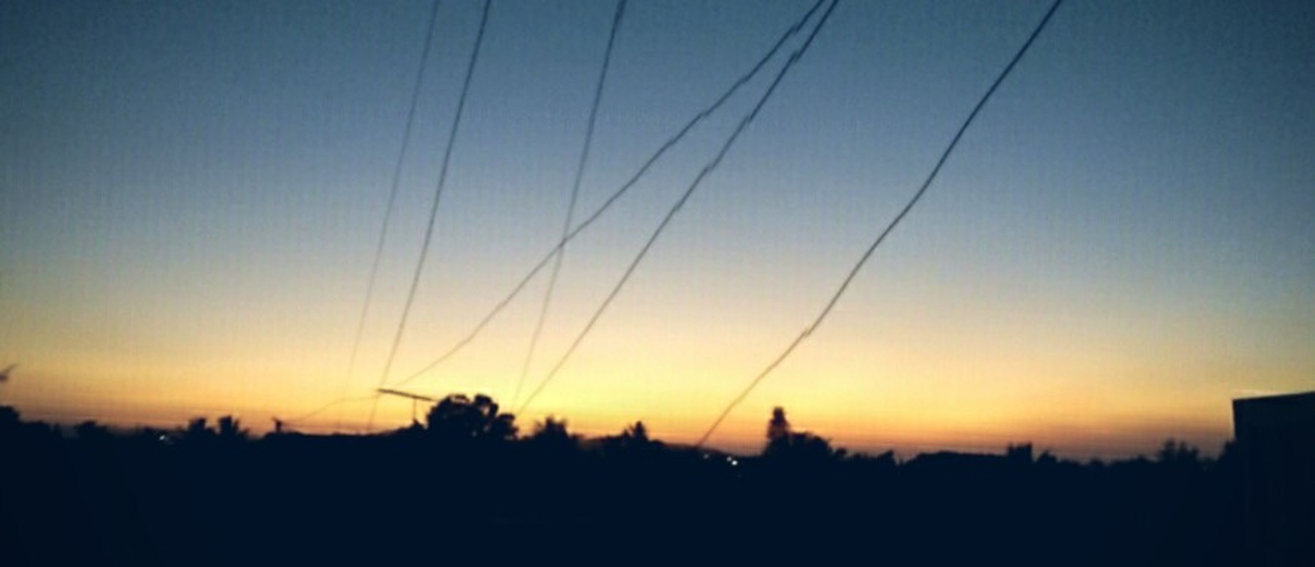 silhouette, sunset, scenics, beauty in nature, tranquility, tranquil scene, orange color, power line, tree, sky, copy space, nature, clear sky, idyllic, electricity pylon, landscape, dark, dusk, no people, electricity