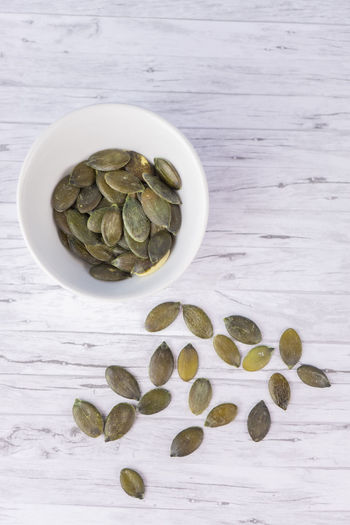 A white cup with pumpkin seeds on a white wood background Pumpkin Seeds Background Seed Isolated Green Food White Wooden Bowl Healthy Snack Closeup Diet Vegetarian Nutrition Ingredient Organic Vegetable Raw Natural Fresh Nature Season  Eat Dry Seasonal Delicious Tradition Group Above View Top Food And Drink Still Life Table Healthy Eating Wellbeing High Angle View Directly Above