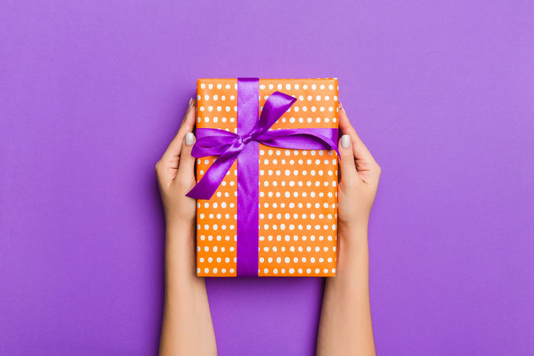 Cropped hands of woman holding gift against purple background