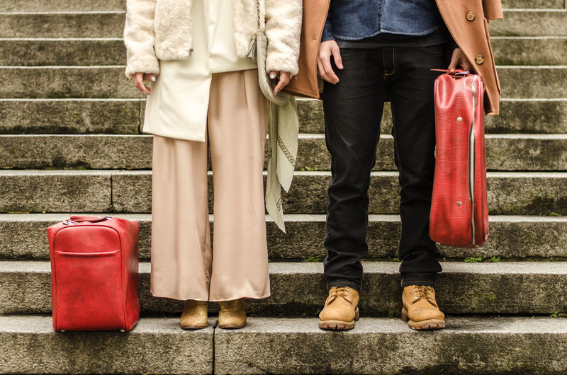 Low Section Of Couple With Luggage Standing On Steps