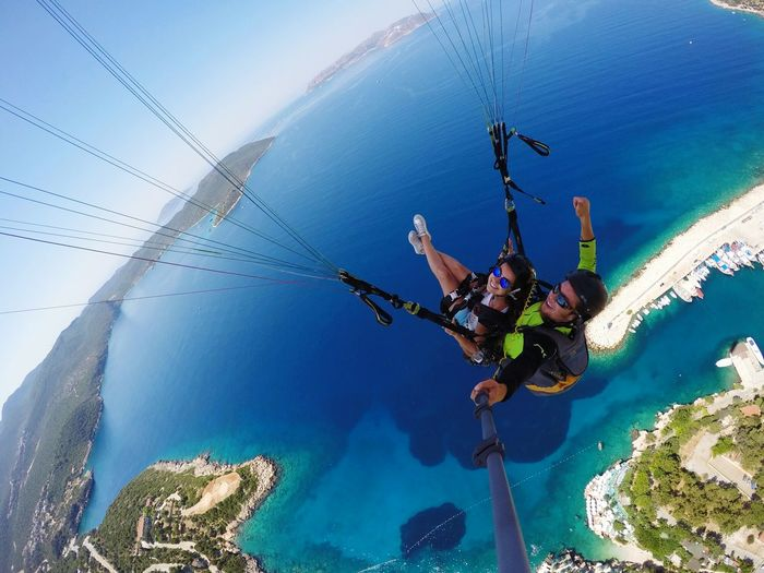 High Angle View Of Couple Paragliding Over Sea Against Sky