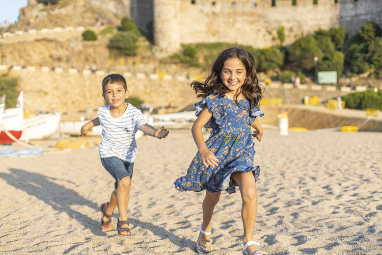 Girl running with brother at beach