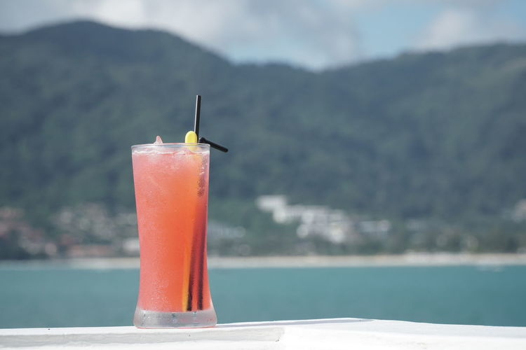 Close-up of cocktail on railing against mountain