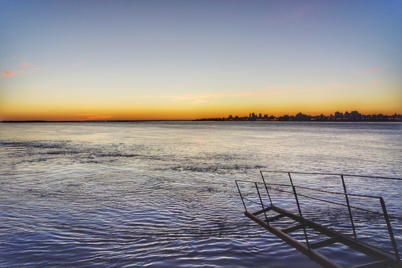 sunset, scenics, no people, water, tranquil scene, beauty in nature, nature, tranquility, sea, outdoors, sky, built structure, clear sky, architecture, day