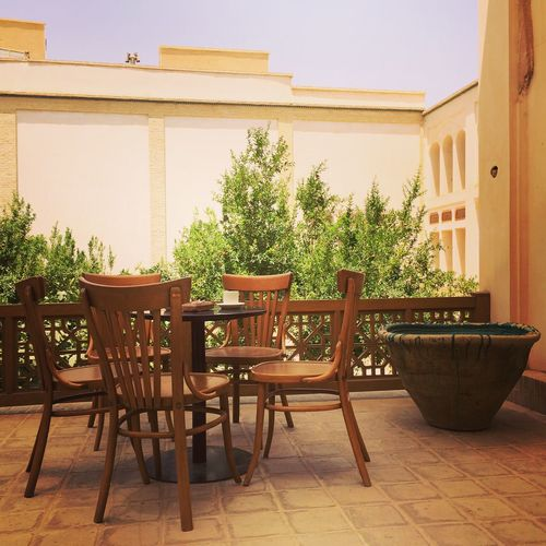 Chairs and table by potted plants against house
