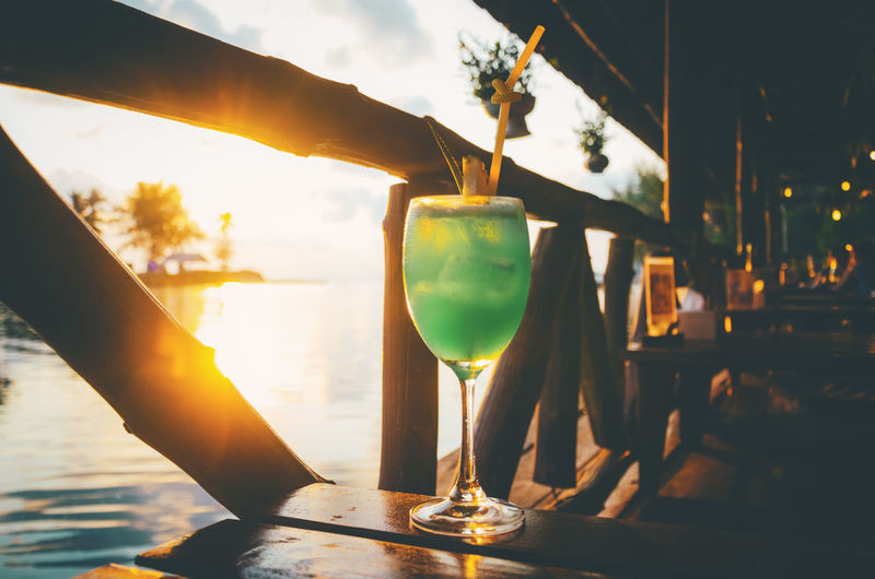Drink Glass Refreshment Alcohol Food And Drink Human Hand Cocktail Hand Drinking Glass Human Body Part One Person Household Equipment Focus On Foreground Sunset Holding Real People Glass - Material Freshness Lifestyles Lens Flare Outdoors Bartender Finger Martini