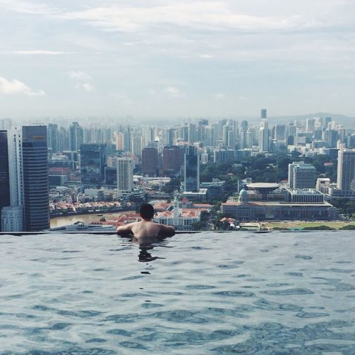 Rear view of man swimming in pool against cityscape