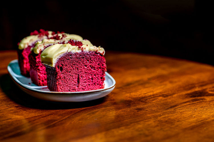 Slices of red velvet cake in a plate on wooden table