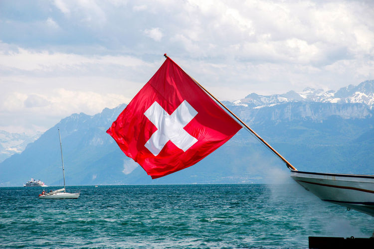 Red flag on lake against sky