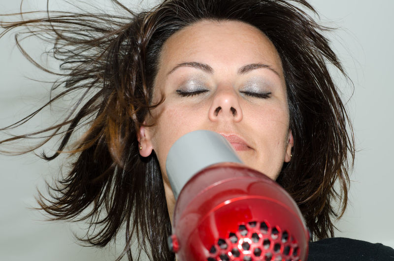 Close-up of young woman using blow dryer on brown hair
