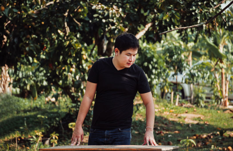 Young man standing by table against trees