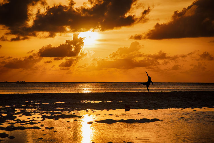 Silhouette person kicking at beach against sky during sunset