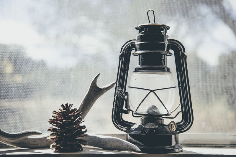 A vintage lantern, an antler, and a pinecone Arizona Lantern Lanterns Light Natural Old-fashioned Vintage Style Antler Cabin Close Up Close-up Collection Deer Antler Kerry Estey Keith Low Tech Low-tech Living Peaceful Pinecone Simple Simple Beauty Simplicity Still Life Unplugged Vintage Window