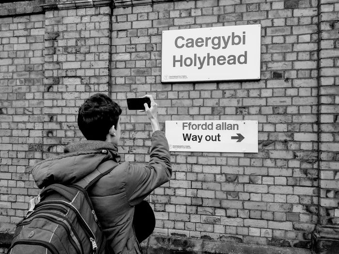 "a man takes a picture of two words in Welsh, meaning ""Holyhead"" and ""Exit"" Curiosity Welsh Language Translation Train Station Ferry Indication Way Out Exit Road Sign Communication City Street Name Sign Guidance Text Placard Brick Wall Standing Men Warning Arrow Sign Information Sign Capital Letter No Parking Sign Information Signboard Directional Sign One Way Arrow Symbol"