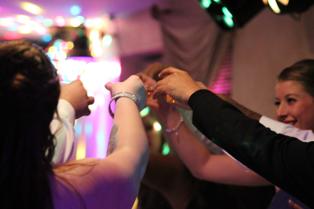 celebration, human hand, night, togetherness, illuminated, leisure activity, indoors, women, real people, human body part, men, friendship, close-up, people