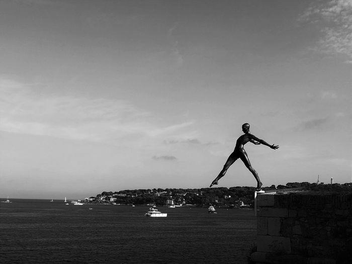 Statue at beach against sky