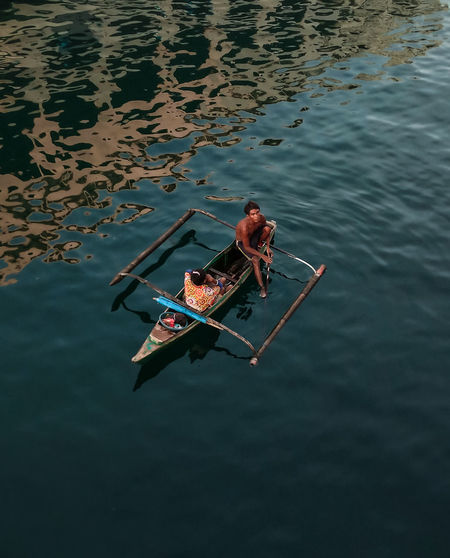 High angle view of man sitting in lake