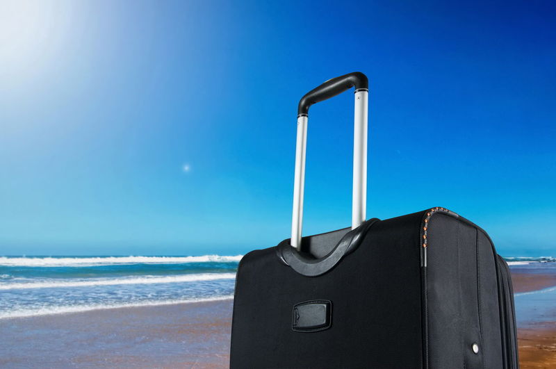 Close-Up Of Suitcase At Beach Against Blue Sky