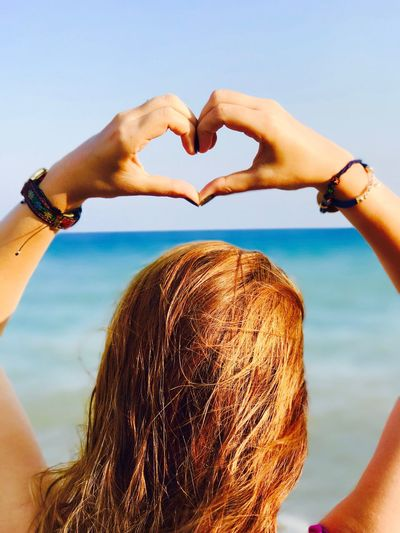 Rear view of woman gesturing heart shape against sea